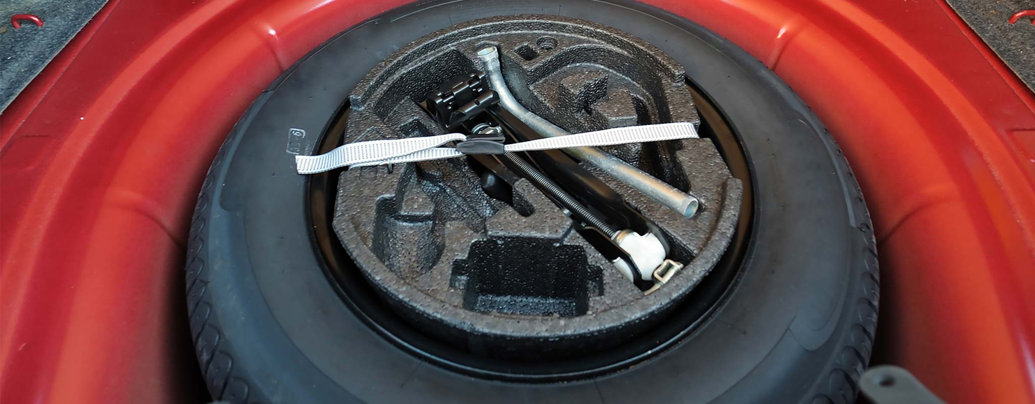 A spare tire in a car trunk.