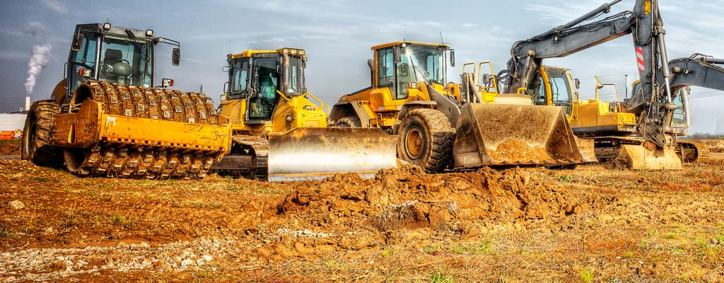 A row of construction equipment lined up in a dirty filled construction site.