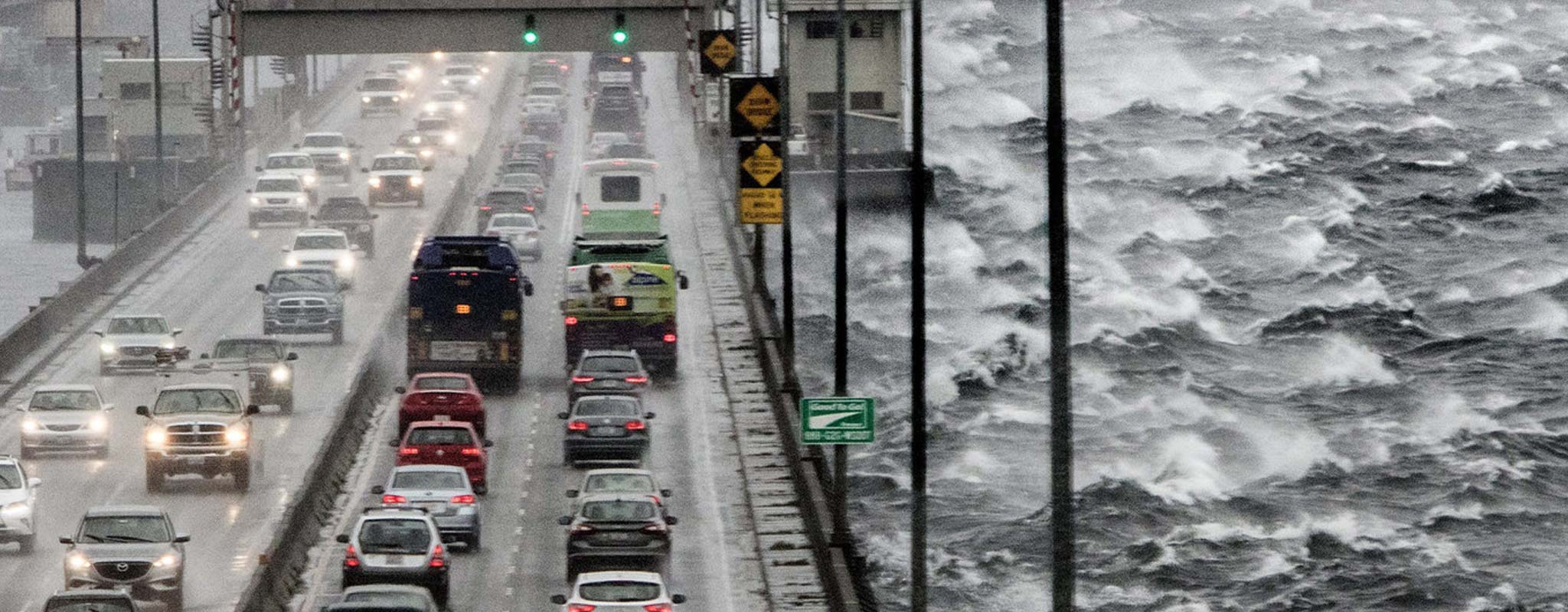 Cars driving over bridge in high winds with white caps on the water.