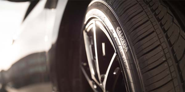 Up close photo of a passenger car tire on a vehicle.
