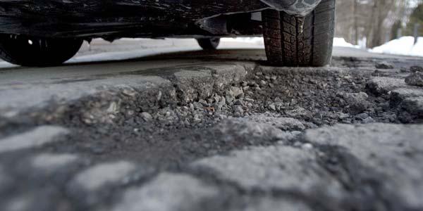 A car tire about to go through a pothole.