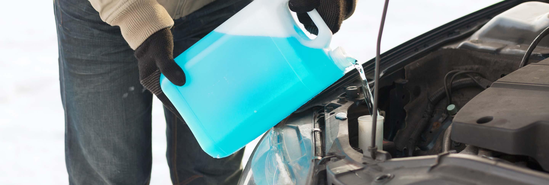 A man adding anti-freeze to his car.