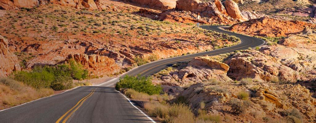 A two-lane road zig-zags through desert scenery.