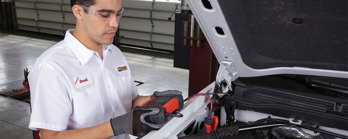 Technician checking auto battery charge