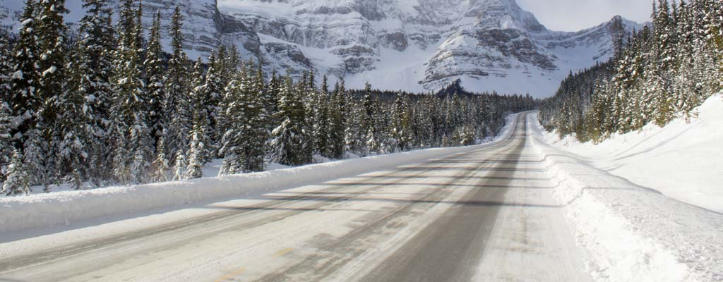 Icy mountain road with steep mountains in the distance.