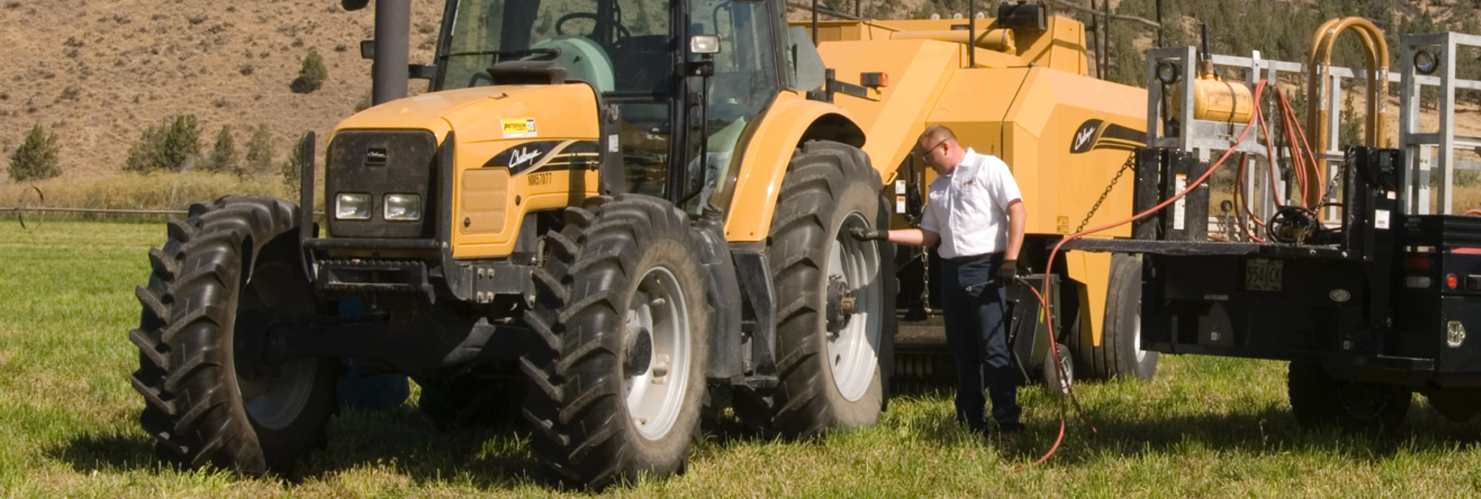 A Les Schwab technician examines a tractor tire's pressure out in the field