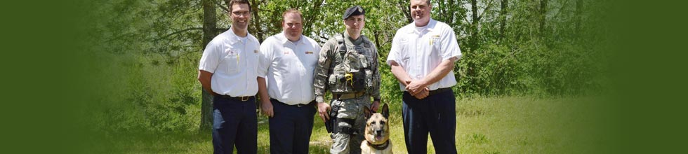 Three Les Schwab managers pose with a military dog and its owner, Frank Wehner.