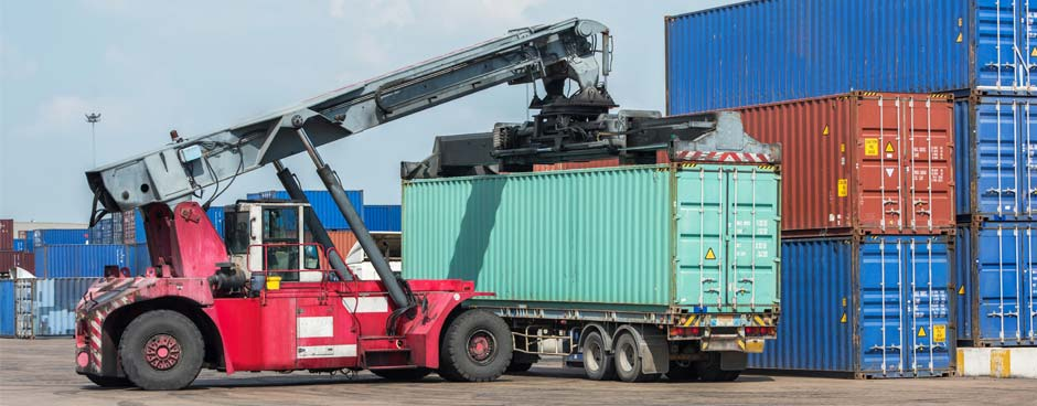 Container handler moving cargo boxes at a port.