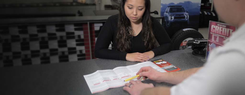 A female customer is applying for a retail credit account at a counter.