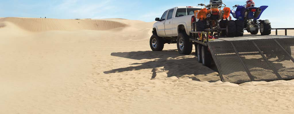 Truck with loaded trailer on sand dunes.