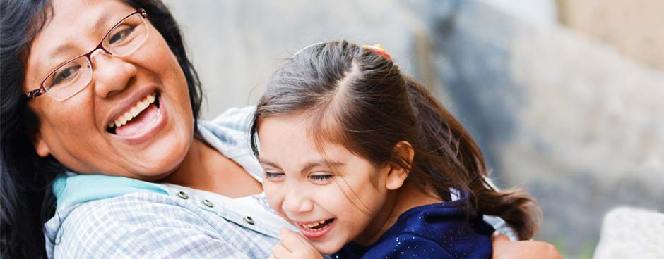 A hispanic mother and daughter laughing.