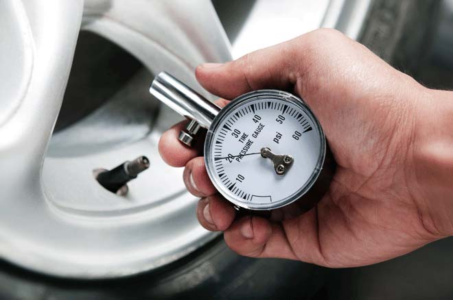Checking tire pressure with a round tire pressure gauge
