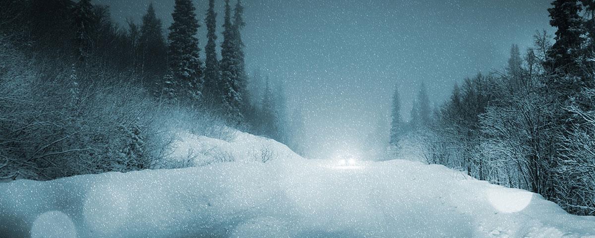 Car traveling dark winter road