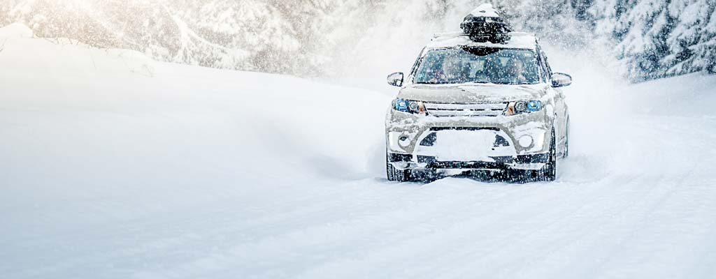 CUV with a cargo carrier driving through snow.