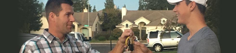Les Schwab manager, Matt Clift hands his son, Lane, a set of car keys.