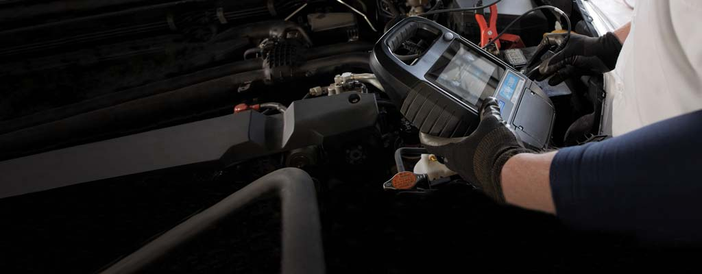 A Les Schwab technician inspecting a car battery that is installed in a vehicle