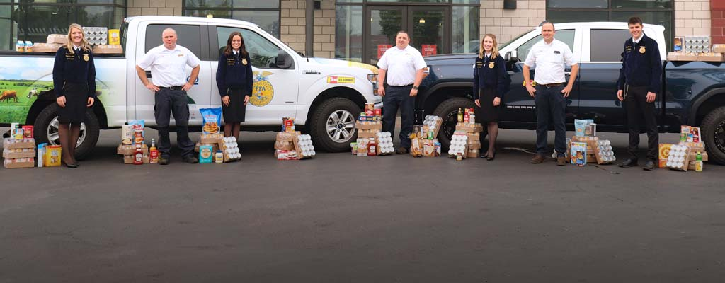 Oregon FFA Members and Les Schwab employees standing in front of a Les Schwab store with donated food.