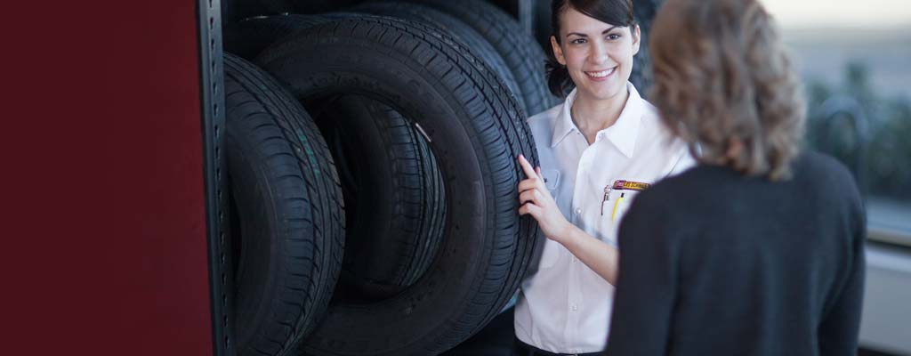 A Les Schwab technician inspects a tire being carted in by another Les Schwab technician.