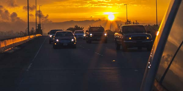 Cars running headlights as the sun sets behind them.