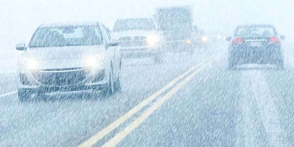 Cars on a driving through snowy weather.
