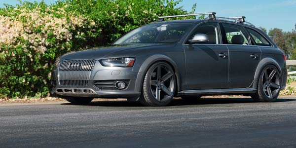 Grey Audi wagon with custom wheel and a roof rack.