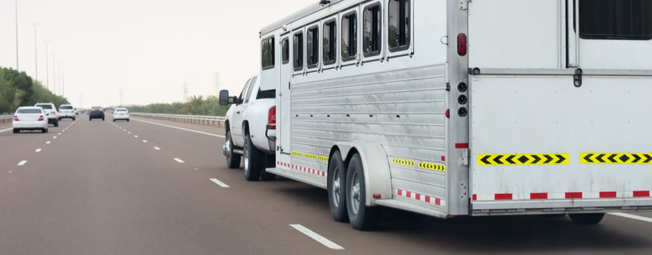A pickup truck tows a trailer down a highway.