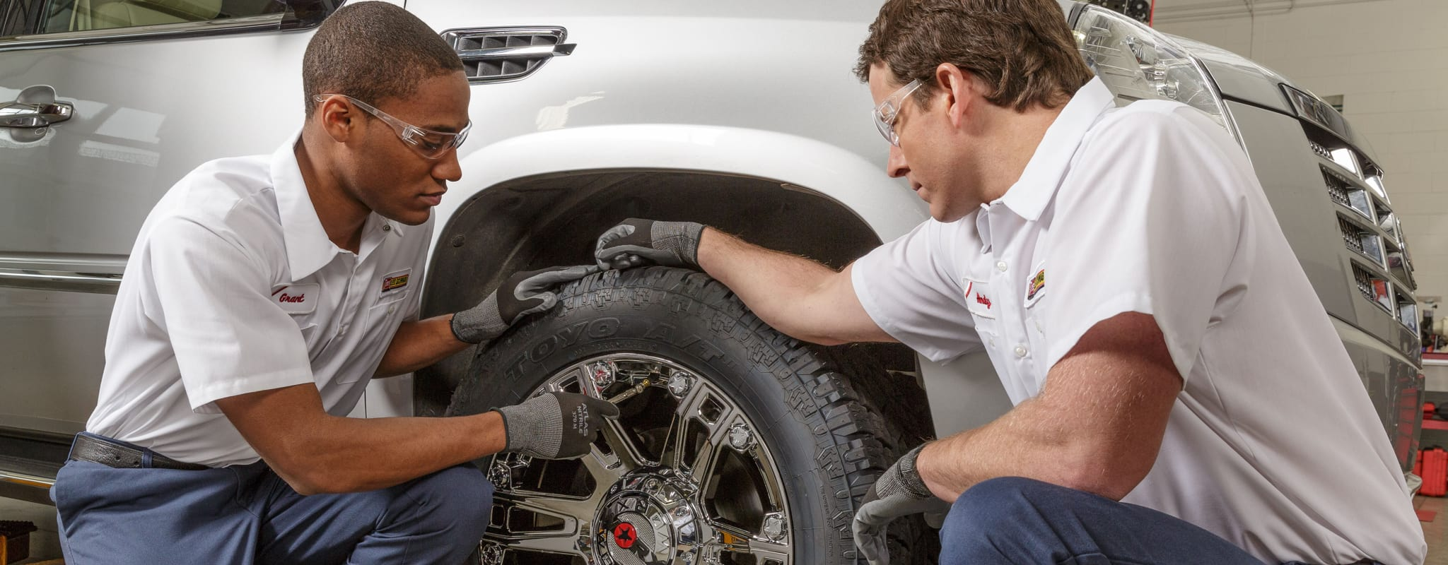 Two Les Schwab technicians examine a tire inside a garage bay.