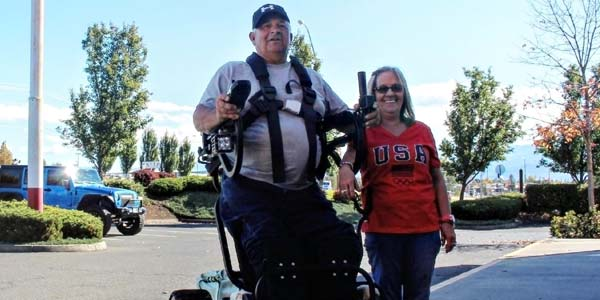 George Myers in a wheelchair that allows him to stand, next to wife Debbie.
