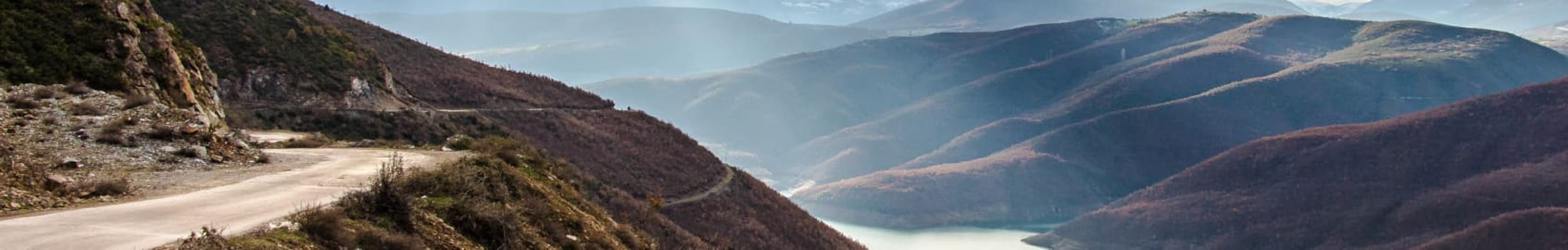 A twisting road cut into the side of a mountain, with a steep dropoff to the river below.
