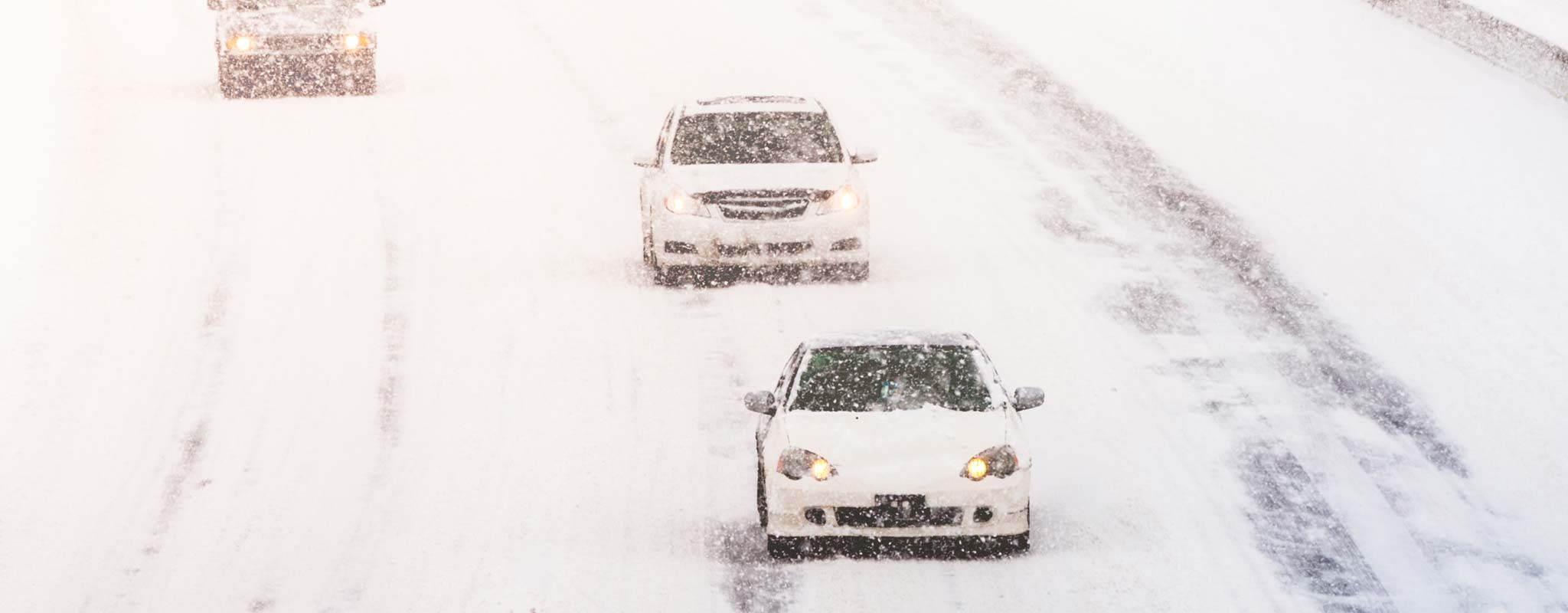 Vehicles on a snowy freeway.