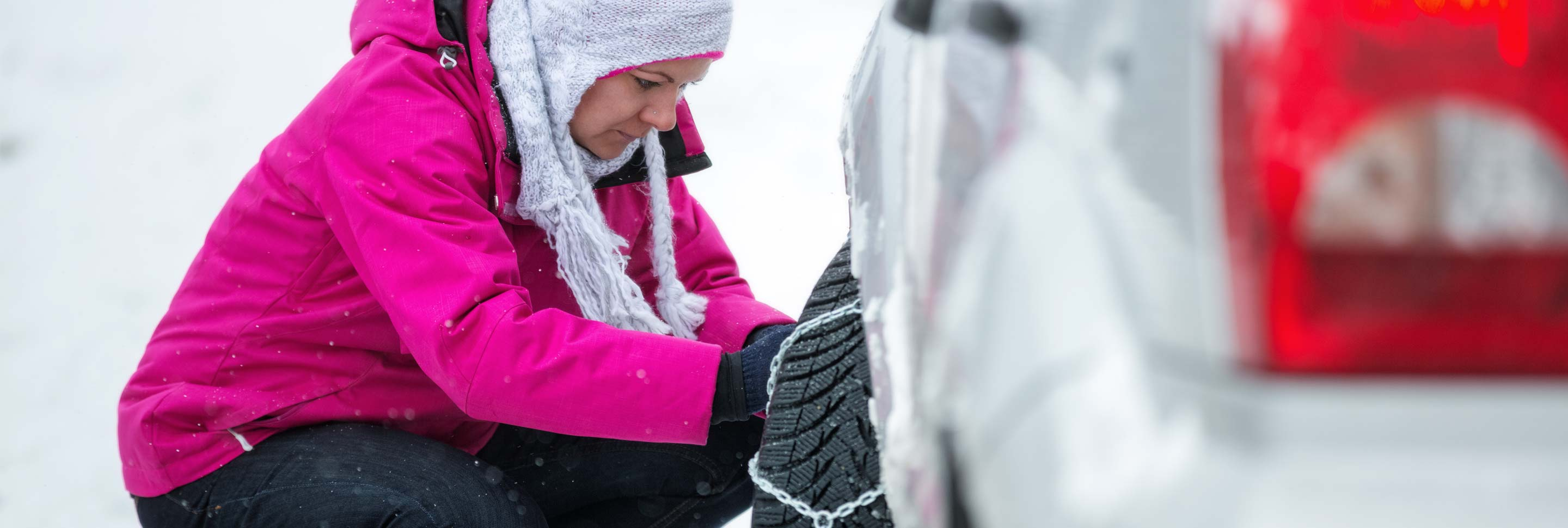 A woman putting chains on her snow tires.