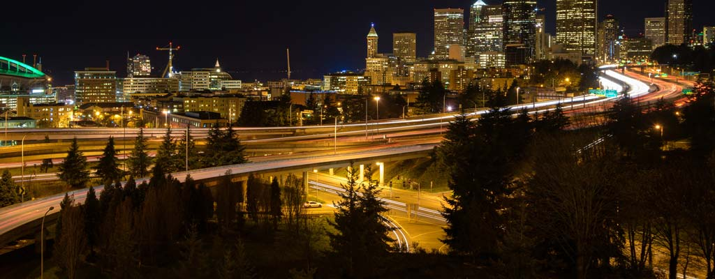 Seattle freeway and skyline at night with car light trails.