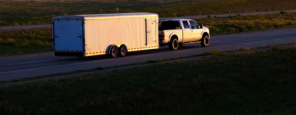 Pickup pulling long utility trailer at dusk