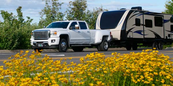 White truck pulling a long travel trailer.