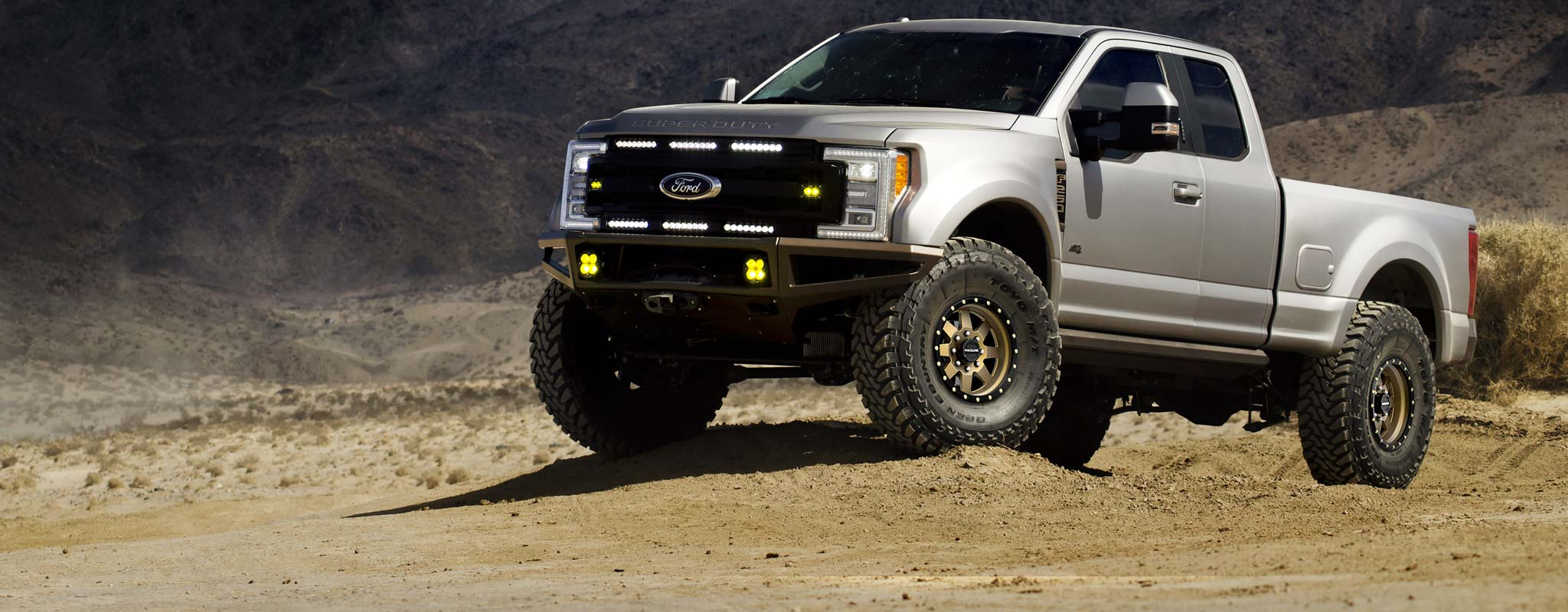 A Ford F-250 with custom wheels parked in the desert