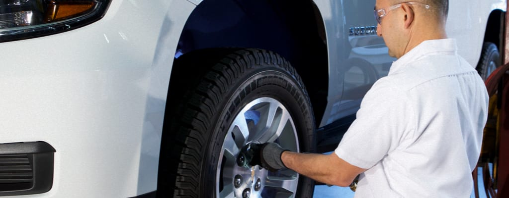 A Les Schwab technician installing winter tires