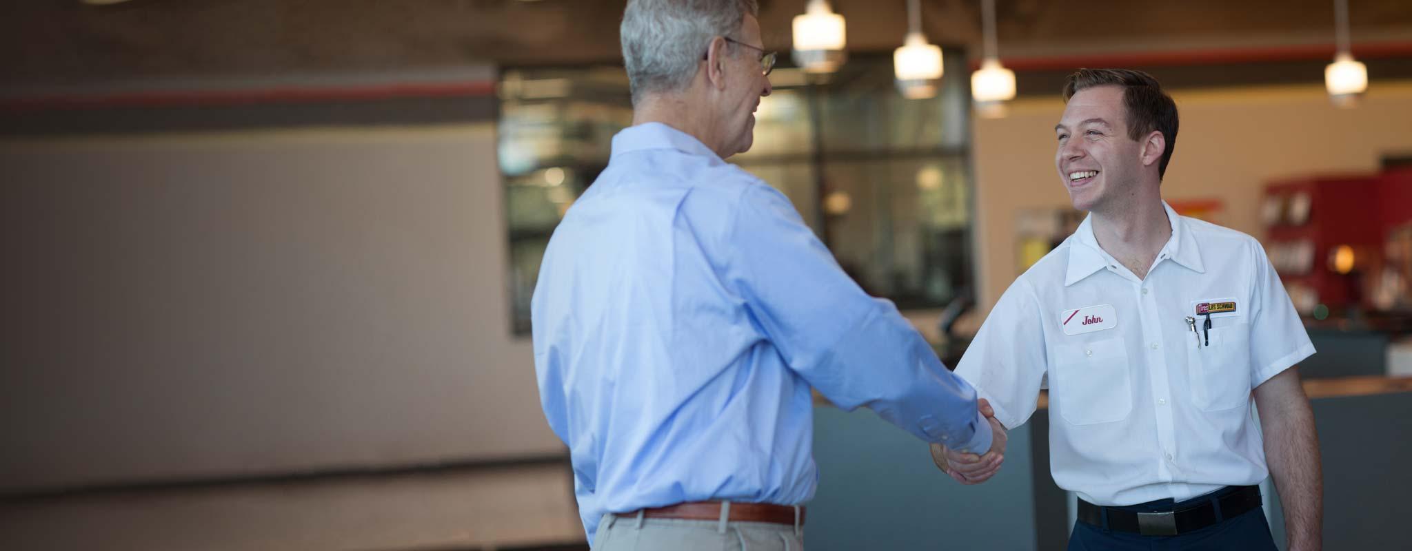 Les Schwab employee shakes a customers hand.
