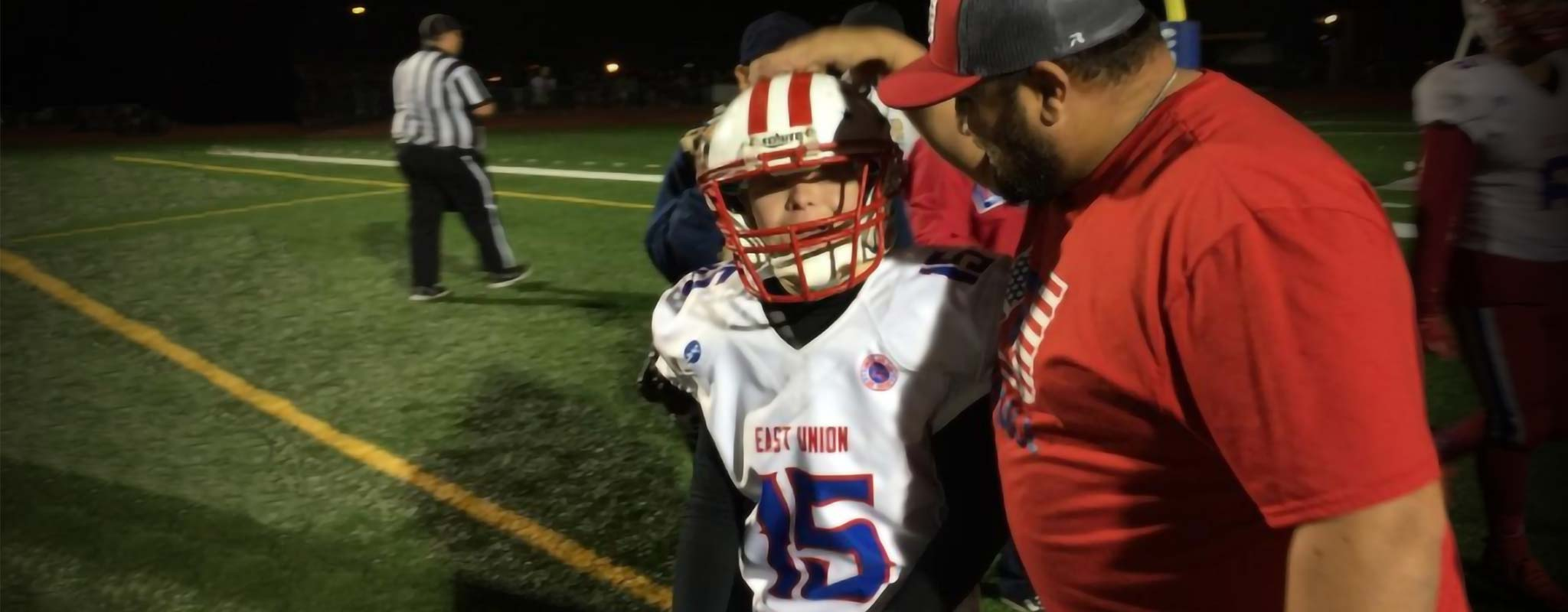The East Union high school football coach pats a player on their head.