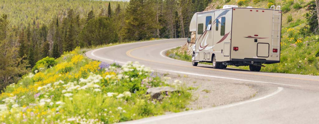 Tan motorhome going down a rural highway