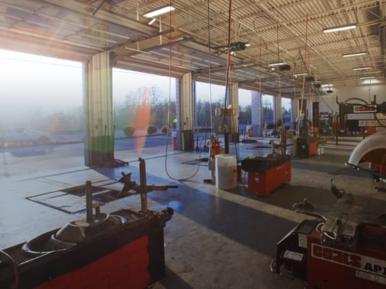The inside of a wide Les Schwab garage, with all doors open.