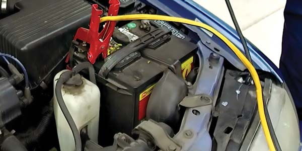 A car battery under the hood with jumper cables attached.