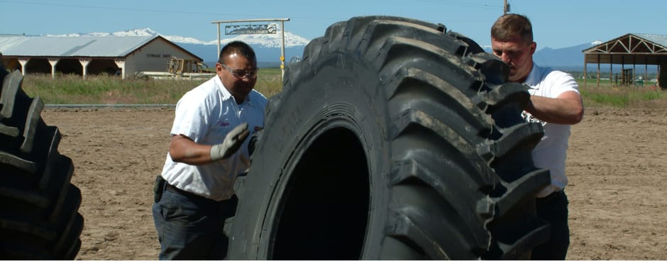 Two Les Schwab Employees moving tire through field