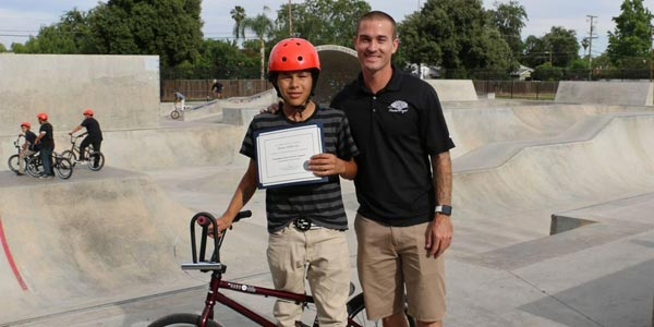 Brani Valencia and Tony Hoffman pose at a skatepark.