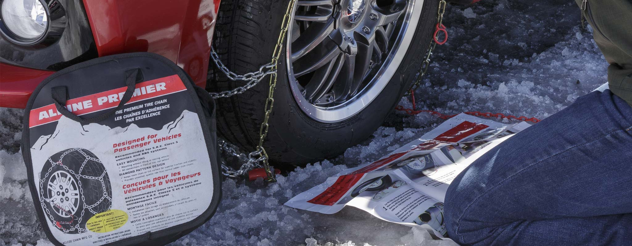 A person putting snow chains on their passenger vehicle.