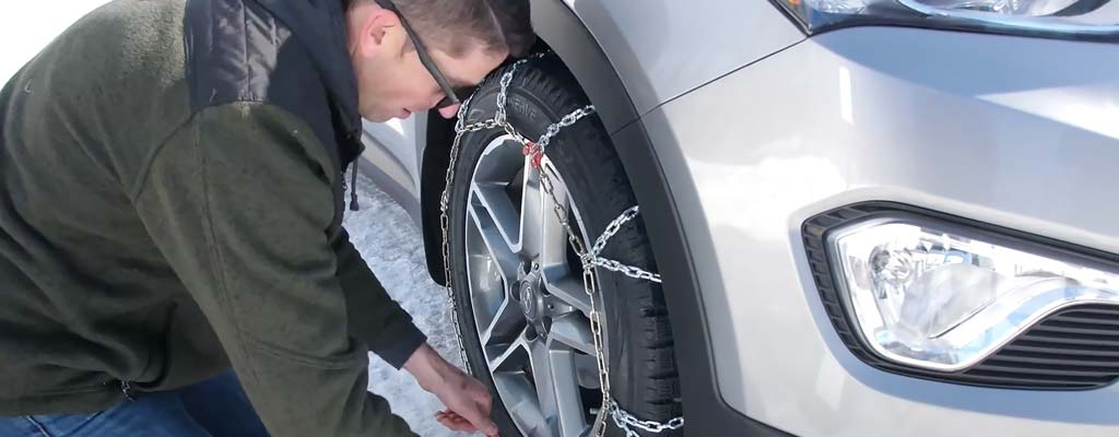 A man putting snow chains on their CUV.