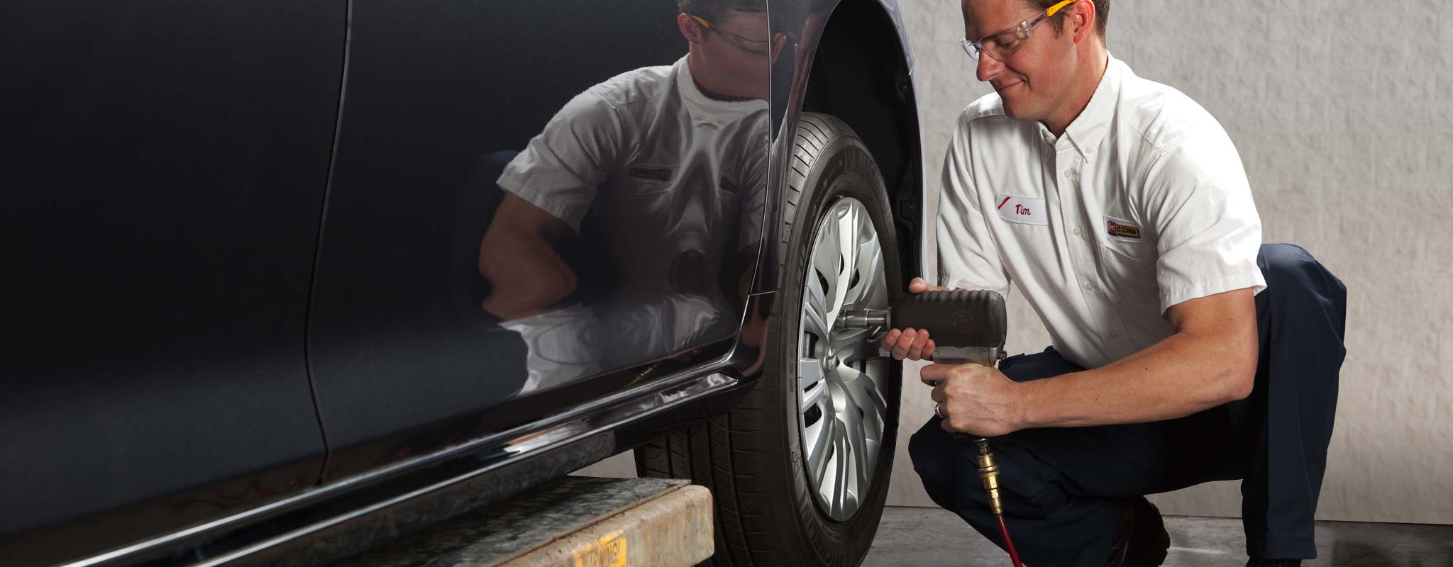 A tire technician using an air gun to remove lug nuts from a tire.