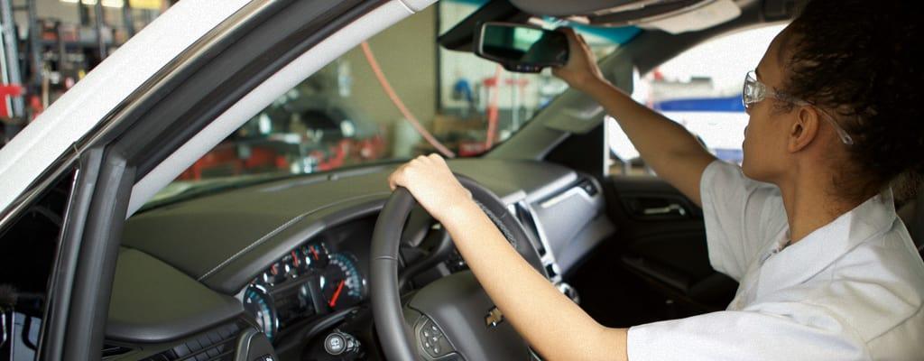 A Les Schwab technician readjusts a rearview mirror