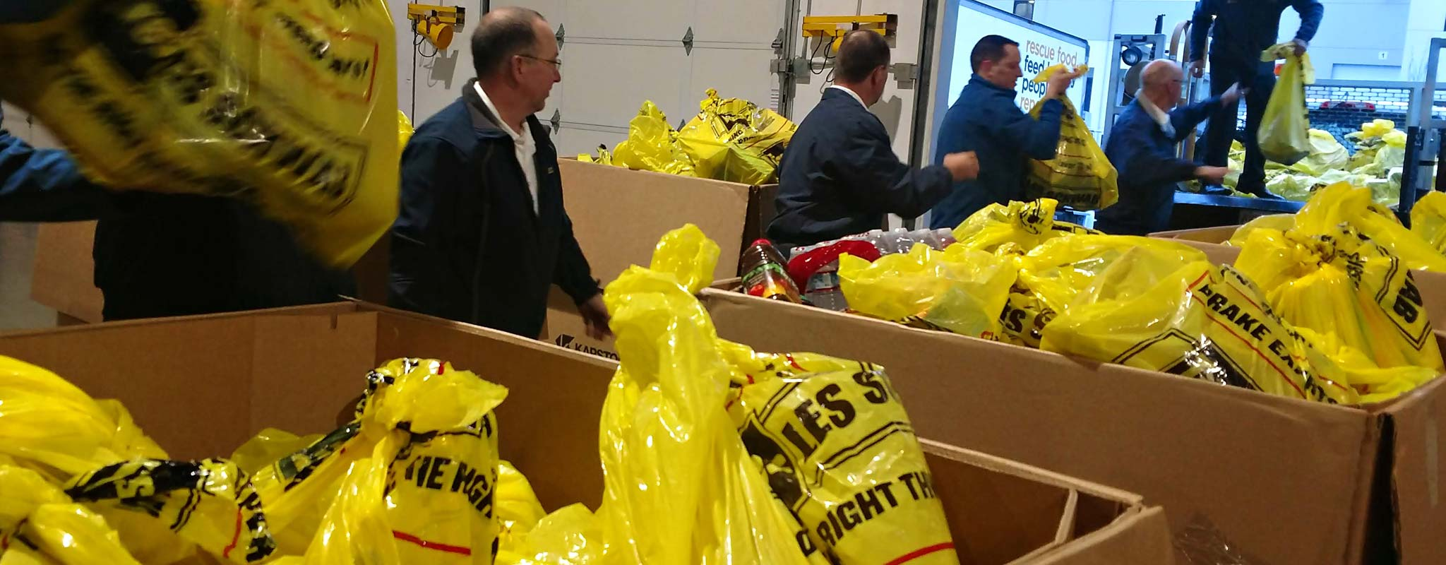 Les Schwab employees transferring collected food to a vehicle for delivery.