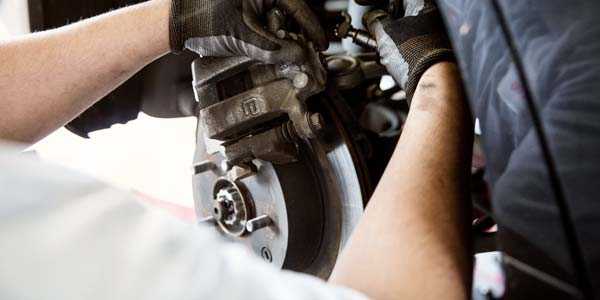 Close up view of a technician working on a brake system.