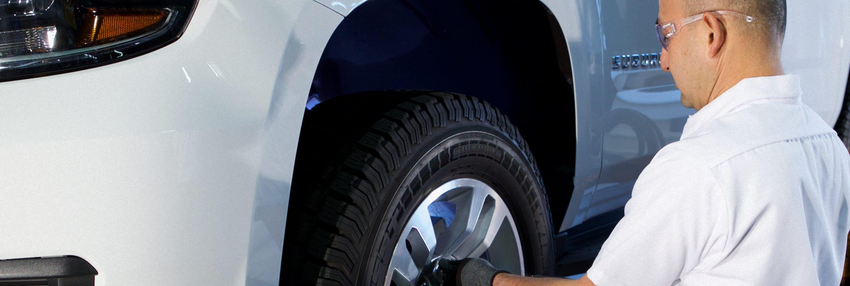 A Les Schwab technician installing winter tires